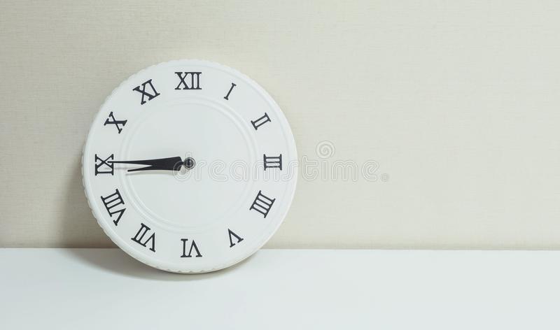 Closeup white clock for decorate show a quarter to nine or 8:45 a.m. on white wood desk and cream wallpaper textured background wi royalty free stock photo