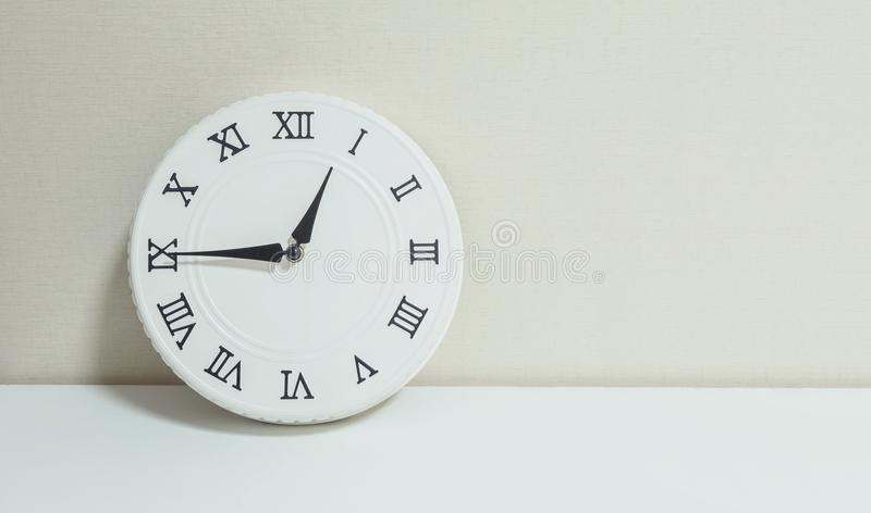 Closeup white clock for decorate show a quarter to one p.m. or 12:45 p.m. on white wood desk and cream wallpaper textured backgrou stock photography
