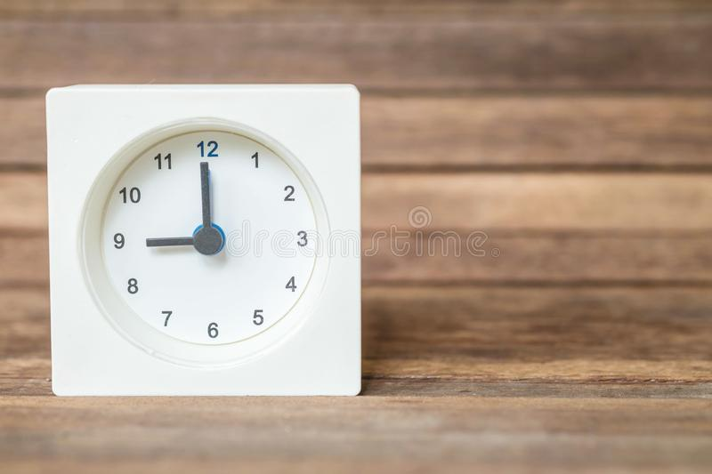 Closeup white clock showed nine o `clock on blurred brown wood board background stock photography