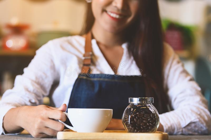 Closeup of white coffee cup with beautiful Asian woman barista background for serving to customer. Job and occupation. Food and stock photos