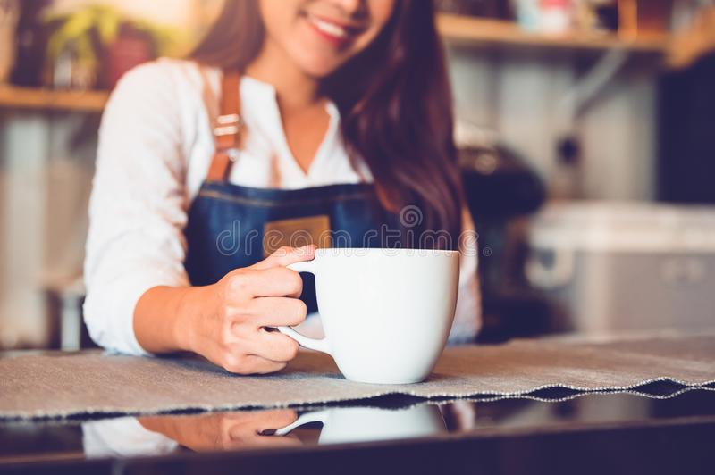Closeup of white coffee cup with beautiful Asian woman barista background for serving to customer. Job and occupation. Food and. Drink beverage. Coffee shop and stock images