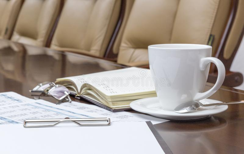 Closeup of white coffee cup on table in empty corporate conference room stock photo