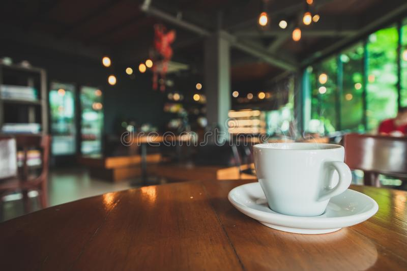 Closeup white coffee mug in coffee shop. Closeup white coffee mug placed on a brown wood table in a coffee shop stock photos