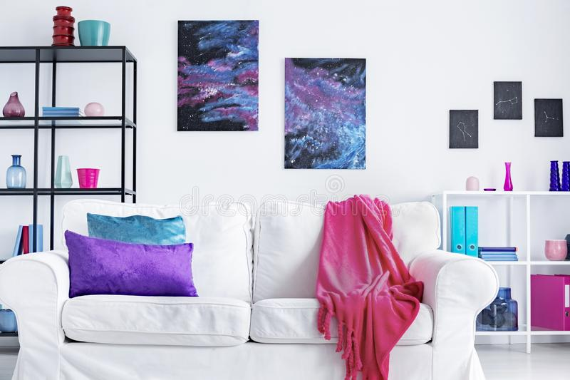 Closeup of white comfortable couch with pink blanket and purple and blue pillows in modern living room interior, real photo royalty free stock photos