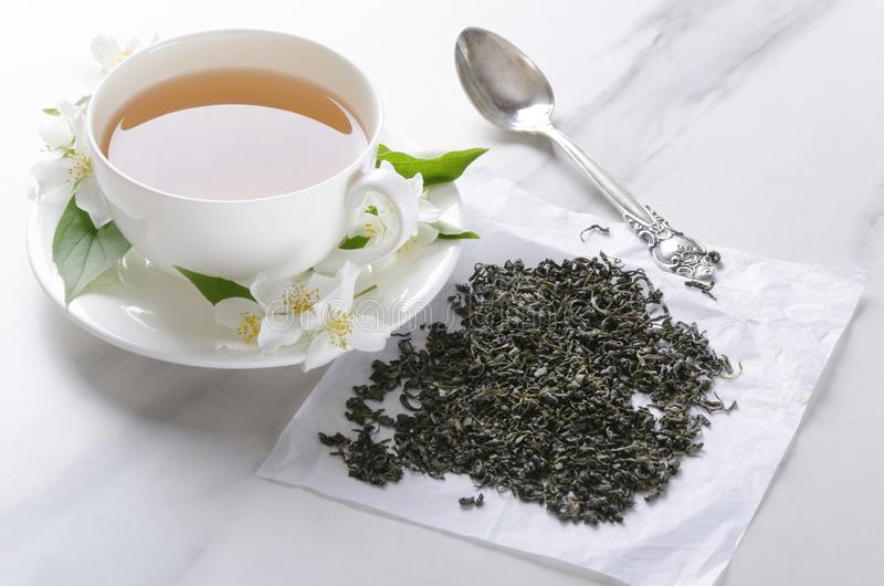 Closeup of white cup of green hot tea with jasmine flowers, vintage spoon, dry leaves of tea on the white table royalty free stock photography