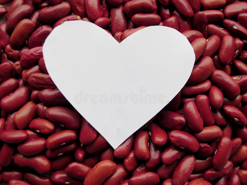 Closeup of White Heart shape on Raw Red Kidney Beans Background stock image