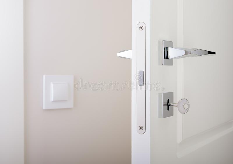Closeup of white interior doors. Lock with key and chrome door handle royalty free stock image