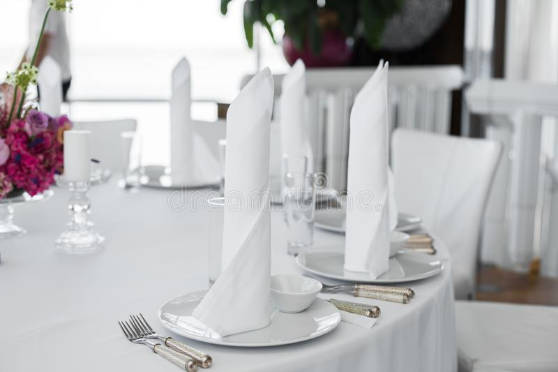 Closeup white napkins stand in  white plates on served table in the restaurant. clean white dishes layout on a white tablecloth. Closeup white napkins stand in stock image