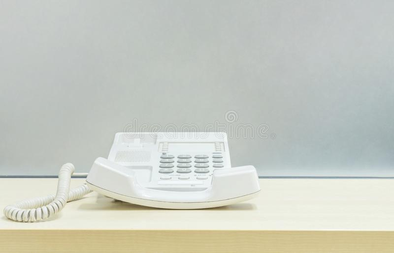 Closeup white phone , office phone on blurred wooden desk and frosted glass wall textured background in the work office. Closeup white phone , office phone on royalty free stock photography