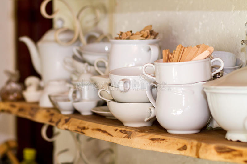 Closeup of white plates and dinnerware in a cupboard royalty free stock images