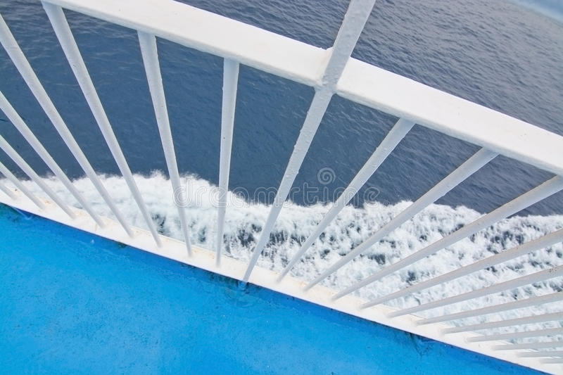 Closeup white railing foamy Mediterranean water stock image