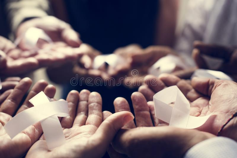 Closeup of white ribbons on people palms for bone cancer awareness and anti-violence campaign stock photography