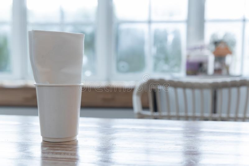 Closeup of white takeaway paper cup with tissue napkin on wooden table royalty free stock photos
