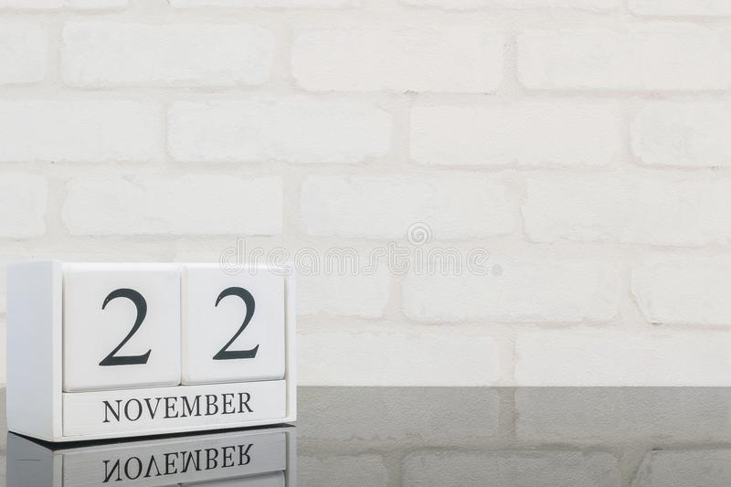 Closeup white wooden calendar with black 22 november word on black glass table and white brick wall textured background with copy. Space stock photo