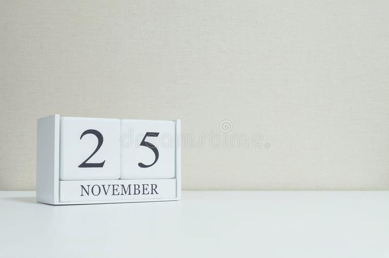 Closeup white wooden calendar with black 25 november word on blurred white wood desk and cream color wallpaper in room textured ba. Closeup wooden calendar with royalty free stock photography