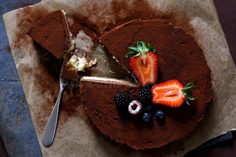 Closeup of whole homemade cheesecake on baking paper with cocoa and fruit topping from above. A slice half eaten royalty free stock image