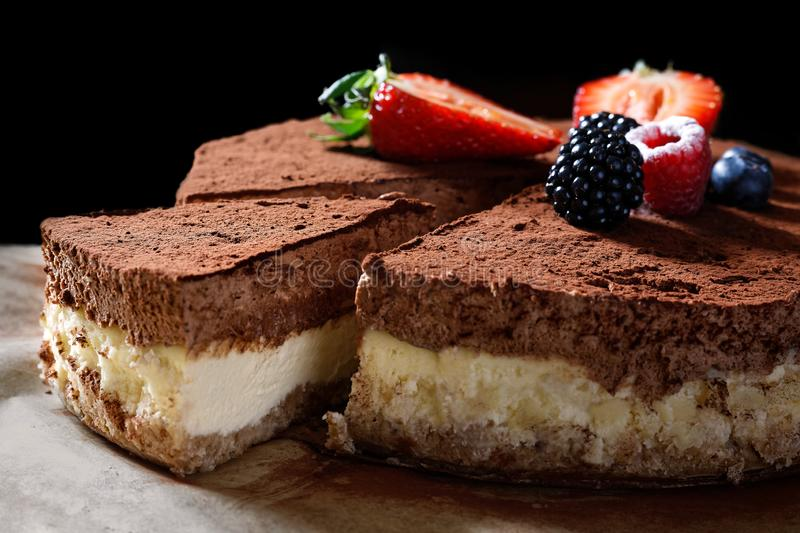 Closeup of whole homemade cheesecake on baking paper with cocoa and fruit topping. A slice cut out royalty free stock photo
