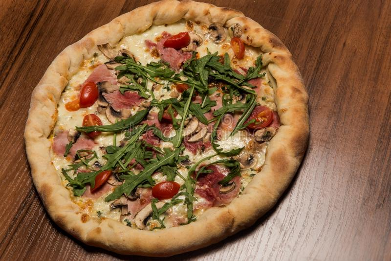 closeup of whole pizza with arugula, ham, mushrooms and tomatoes stock photos