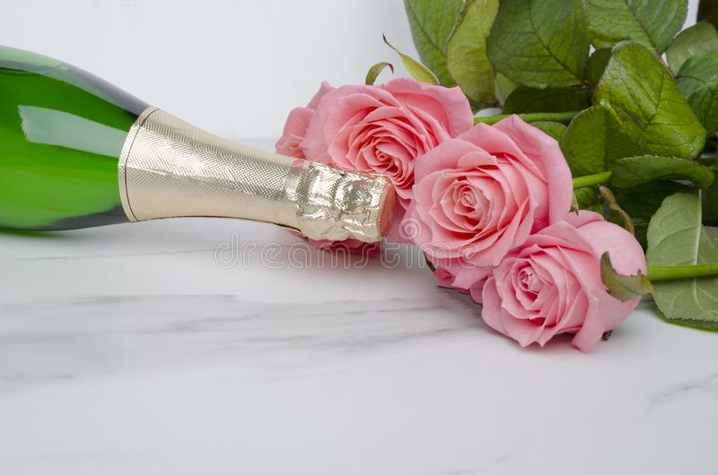Closeup of wine bottle,beautiful roses on white background.Valentine`s day. Top view of flowers,champagne on marble table.Dating concept Top view of wine bottle stock images