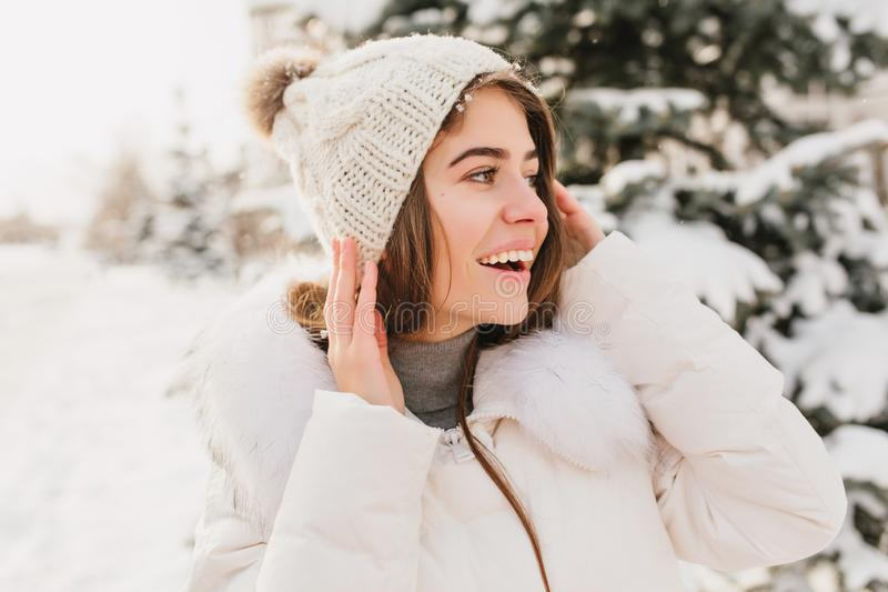 Closeup winter portrait young beautiful woman in white knitted hat expressing to side on street full with snow. Enjoying royalty free stock photo