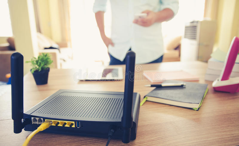 Closeup of a wireless router and a man using smartphone on living room at home ofiice.  royalty free stock images