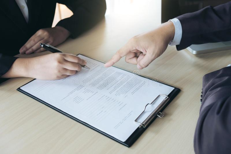 Closeup of woman applicant writing in resume form, person completing filling information and executive pointing help her to sign. In application form, hiring royalty free stock photo