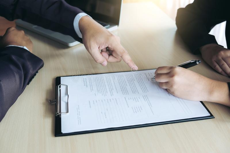 Closeup of woman applicant writing in resume form, person completing filling information and executive pointing help her to sign. In application form, hiring royalty free stock photos