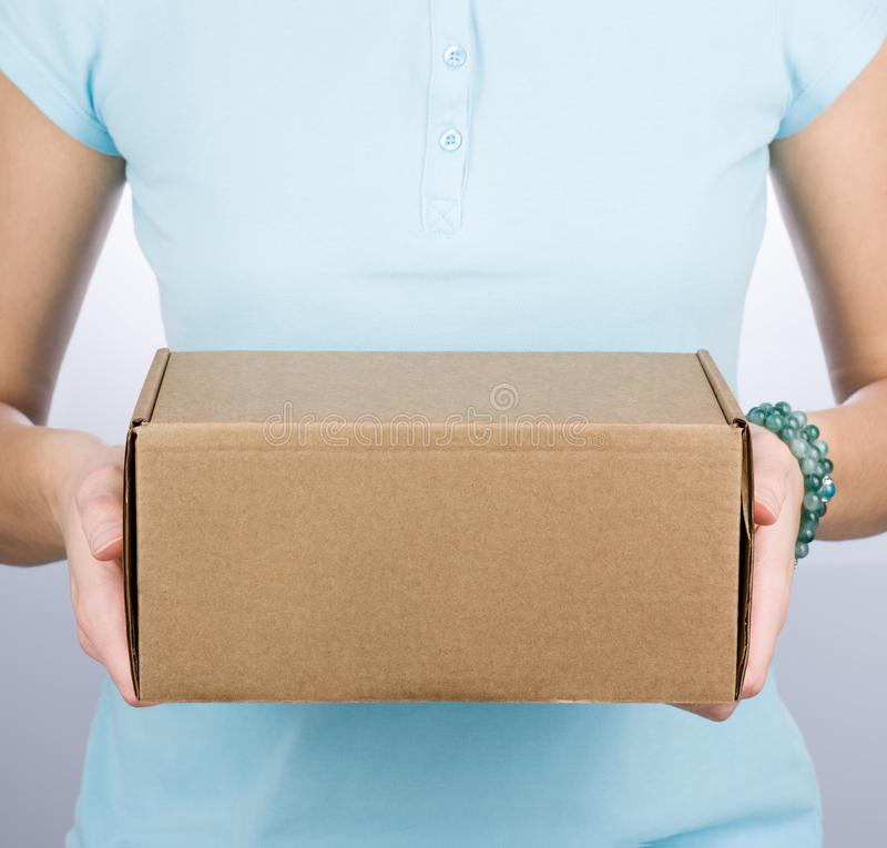 Closeup of a woman in a blue Polo holding a cardboard box royalty free stock photos