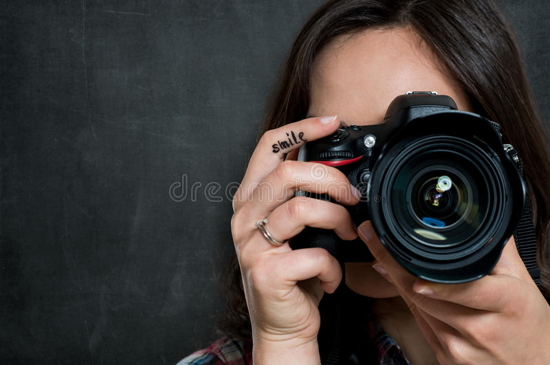 Closeup Of Woman With Camera. Closeup Of Young Woman Using Camera Over Gray Background royalty free stock image