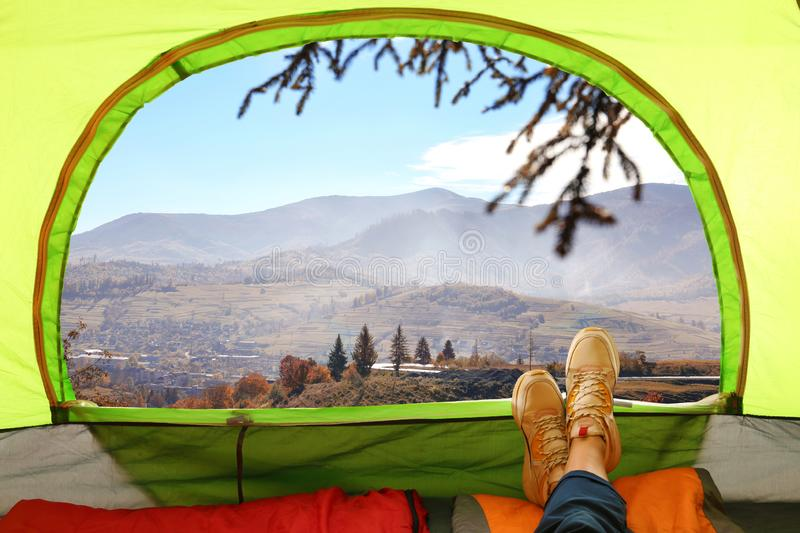Closeup of woman in camping tent with sleeping bags on mountain hill. View from inside royalty free stock photography