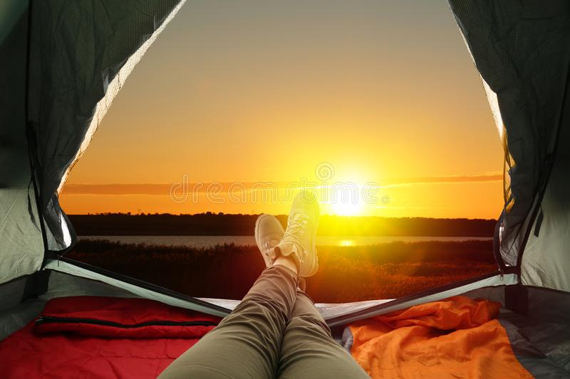 Closeup of woman in camping tent with sleeping bags near river at sunset. View from inside royalty free stock photos