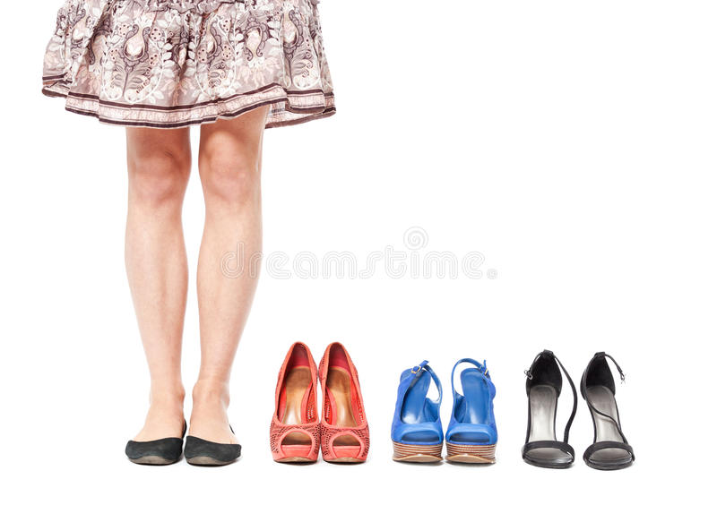 Closeup of woman choosing a pair of shoes - isolated on white. stock photos