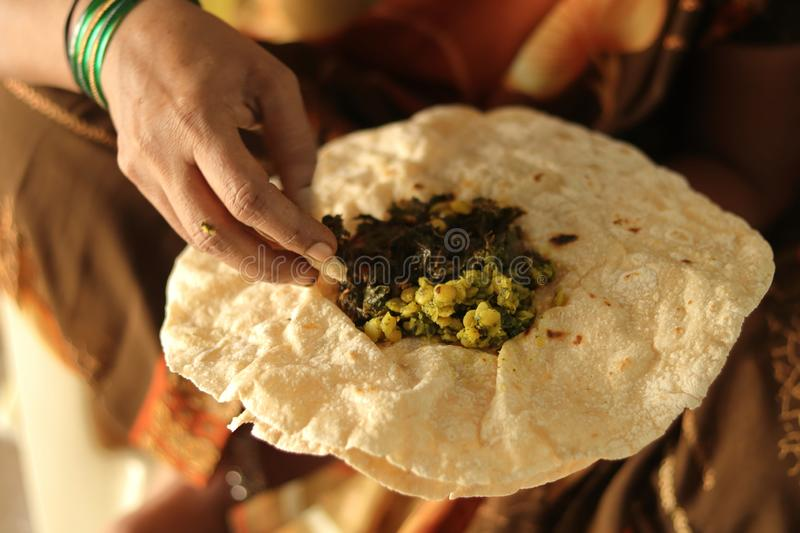 Closeup of woman eating South Indian north Karnataka peoples daily healhy breakfast Jowar roti or rotti or bhakri with dal curry stock image