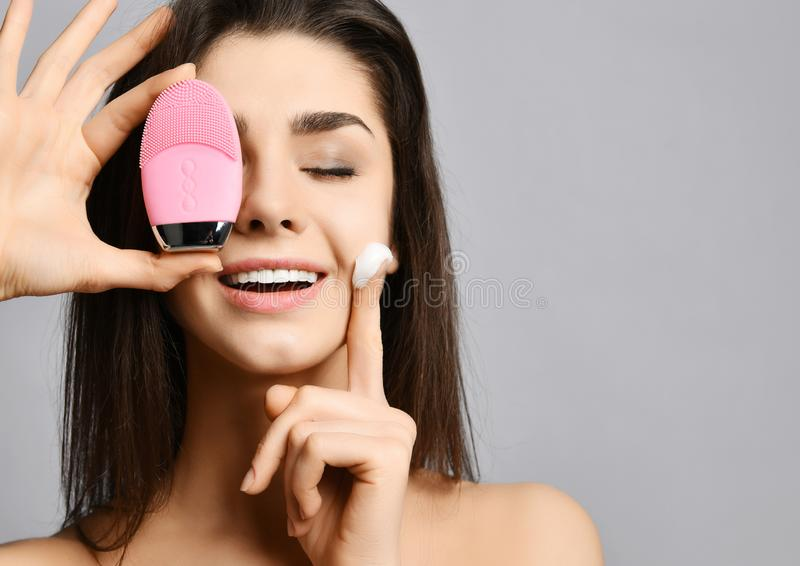 Closeup of pretty woman with pink face exfoliator brush silicone cleansing device for skin and cream and enjoys softness. Closeup of woman with eyes closed with royalty free stock images