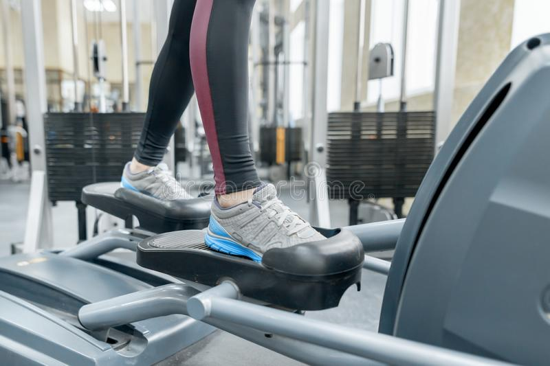 Closeup of woman feet running on treadmill in gym. Fitness, sport, training, people concept stock image