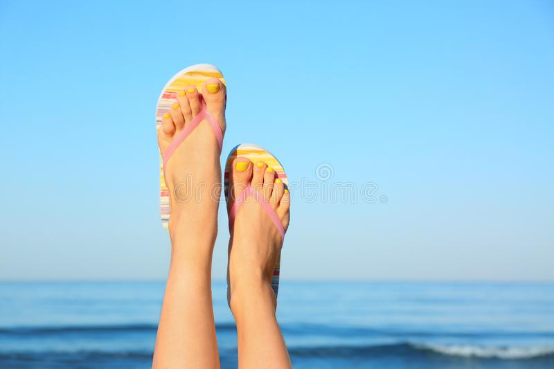 Closeup of woman  flip flops near sea, space for text. Beach accessories. Closeup of woman wearing flip flops near sea, space for text. Beach accessories royalty free stock photos