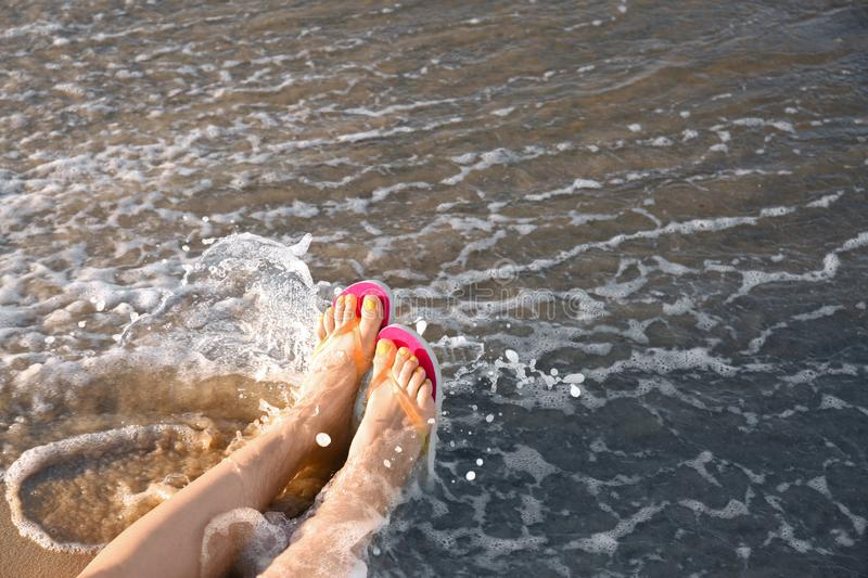 Closeup of woman with flip  on sand near sea, space for text. Beach accessories. Closeup of woman with flip flops on sand near sea, space for text. Beach royalty free stock image