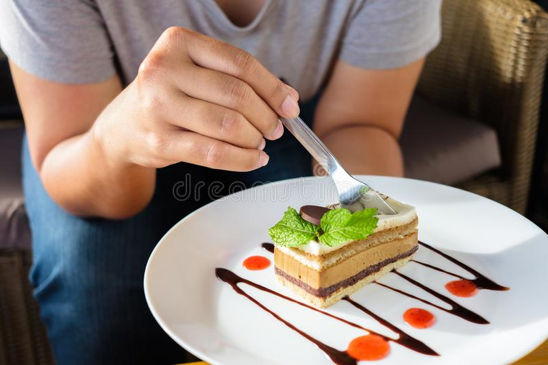Eating Cappuccino Cake. Closeup woman going to eat the cappuccino cake on the white plate stock photos
