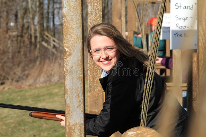 Closeup woman with gun at trap shooting range. Young, blond, caucasian women with her rifle at a trap shooting range stock image