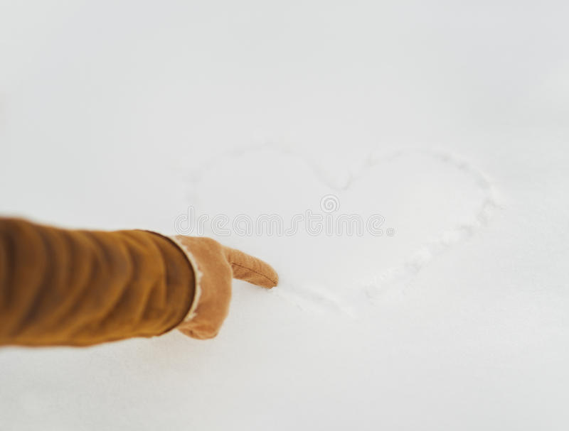 Closeup on woman hand drawing heart on snow. In winter park royalty free stock photography