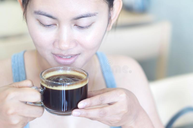 Closeup woman hand holding glass of hot americano coffee for drink with happy face feeling, selective focus, vintage tone stock photography