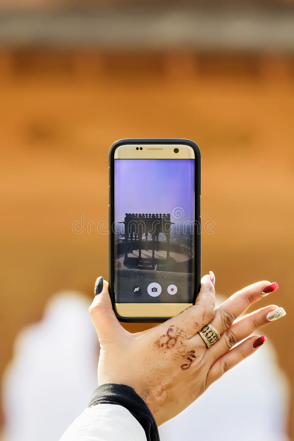 Closeup of woman hand holding smartphone taking photo. Closeup of a woman hand holding a smartphone taking photo of a dome in a fort in Rajasthan, India stock photo