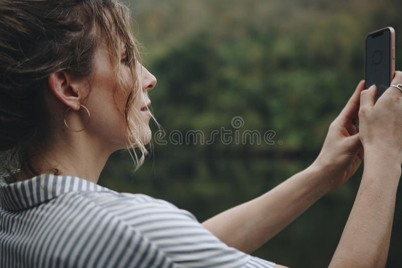 Closeup of a woman hand raising her smartphone up taking a photo of nature travel and tourism concept stock images
