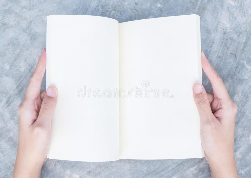 Closeup woman hand read a book in her free time on concrete desk in top view textured background under day light in the garden royalty free stock photos