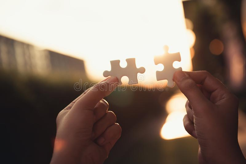 Closeup of woman hands joining pieces of jigsaw puzzle together.,Business solutions stock photography