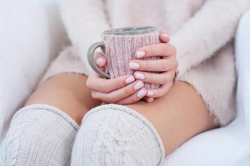 Closeup woman hands with pink manicure holding cup. Closeup woman hands with delicate pink manicure holding decorated cup; knitted knee socks on woman legs stock image
