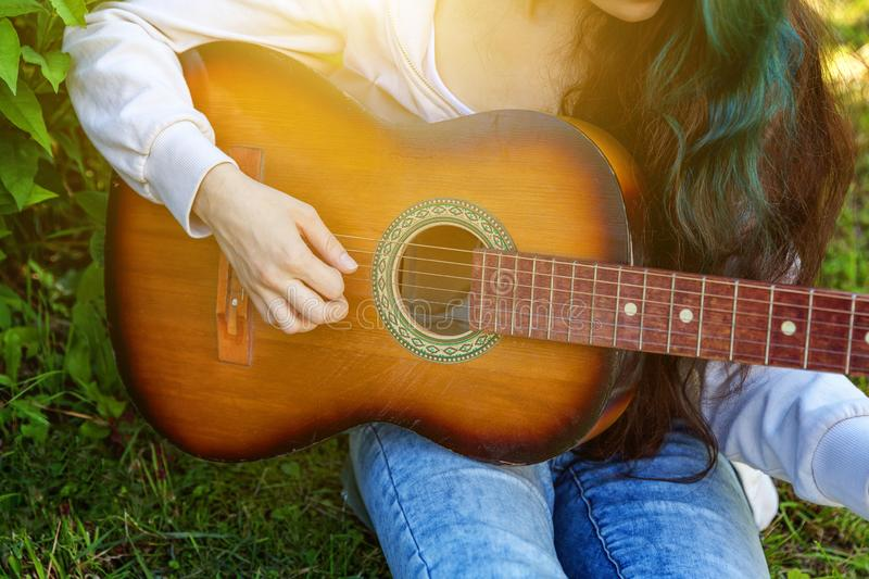 Closeup of woman hands playing acoustic guitar on park or garden background. Teen girl learning to play song and writing music royalty free stock images