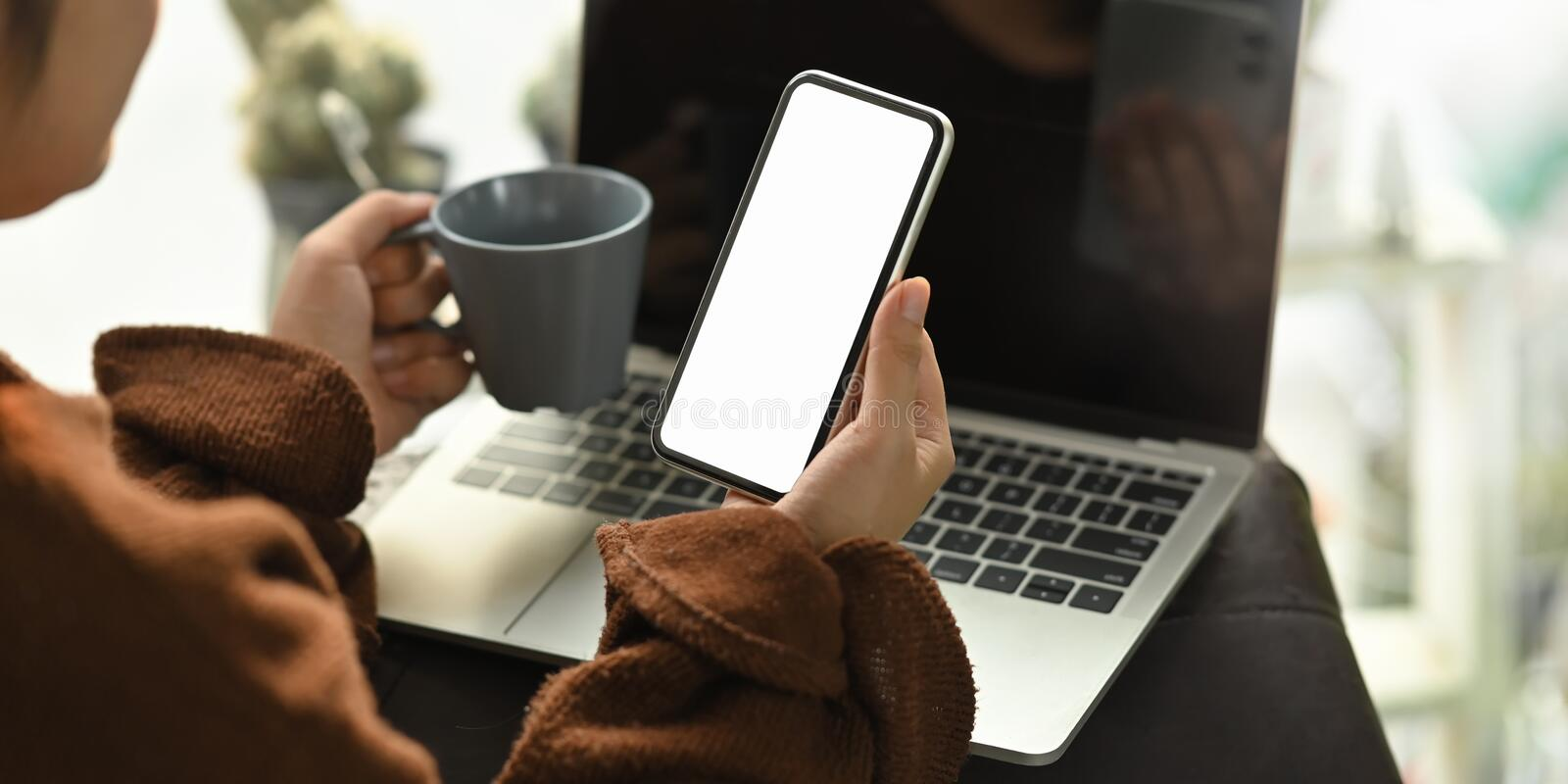 Closeup woman holding a coffee cup and white blank screen smartphone. royalty free stock photography