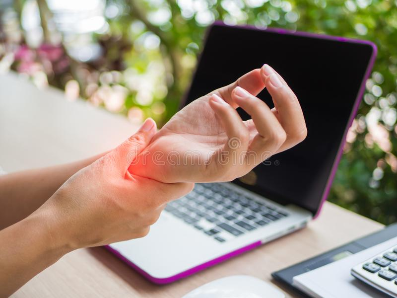Closeup woman holding her wrist pain from using computer. Office syndrome hand pain by occupational disease royalty free stock photo