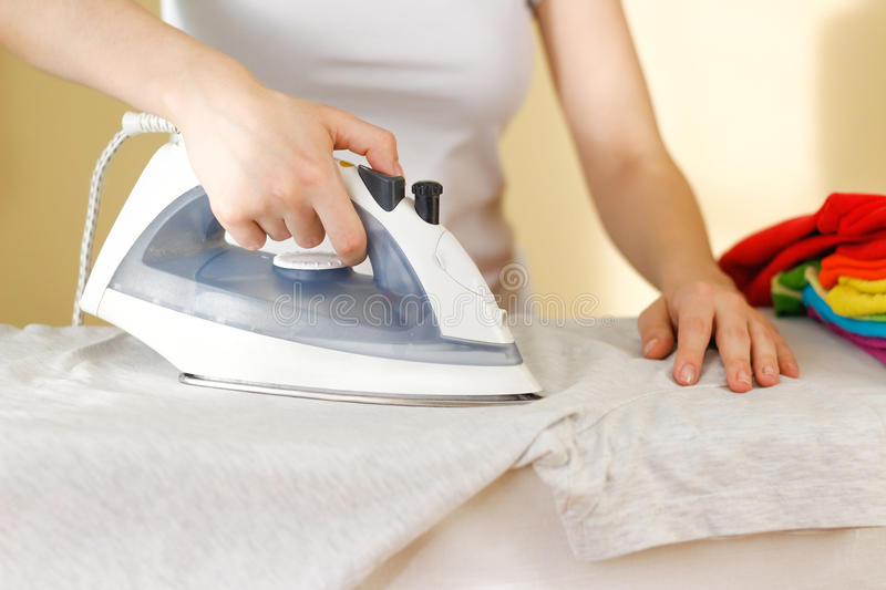 Closeup of woman ironing colored clothes on ironing board. House. Wife uses the home appliance stock photo